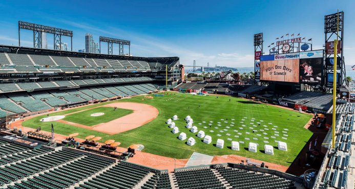 the baseball field at oracle park, with tents and blankets in the outfield facing the large scoreboard screen